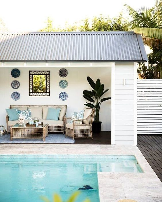 a tropical and beach-inspired pool cabana with decorative plates, rattan furniture, a potted plants and touches of blue
