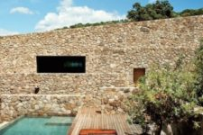 18 a Mediterranean-style deck with trees, a stone wall and a long and narrow pool is very welcoming