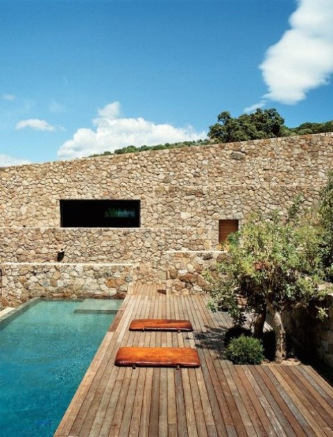 a Mediterranean-style deck with trees, a stone wall and a long and narrow pool is very welcoming