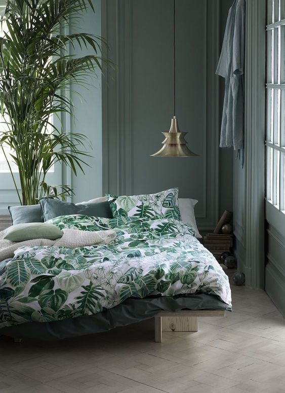 a moody grey bedroom with a botanical bedding set and a large plant in a pot is a stylish idea