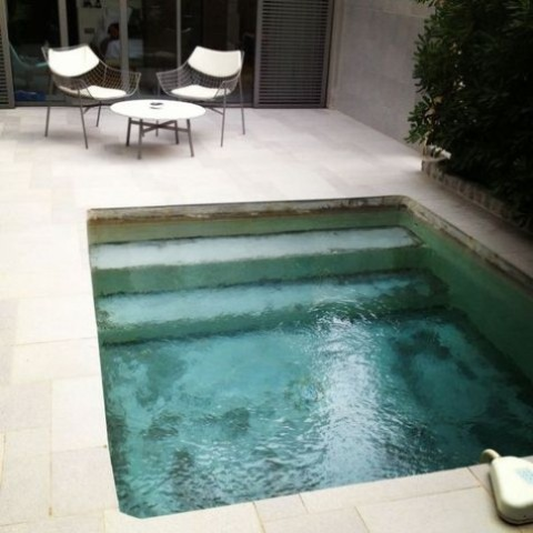 a small backyard fully done with neutral tiles, with stylish wire furniture and a small pool with steps