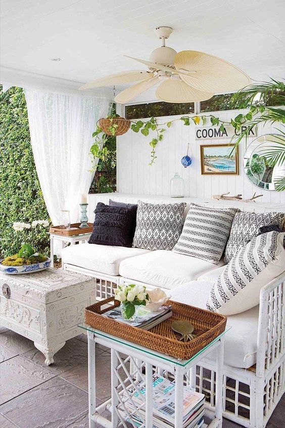 an eclectic pool cabana in white, with a shiplap wall, greenery, baskets, chic coffee tables and a rattan sofa with pillows