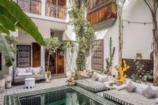 19 a gorgeous Moroccan pool patio with mattresses and pillows, a bench, side tables and potted plants