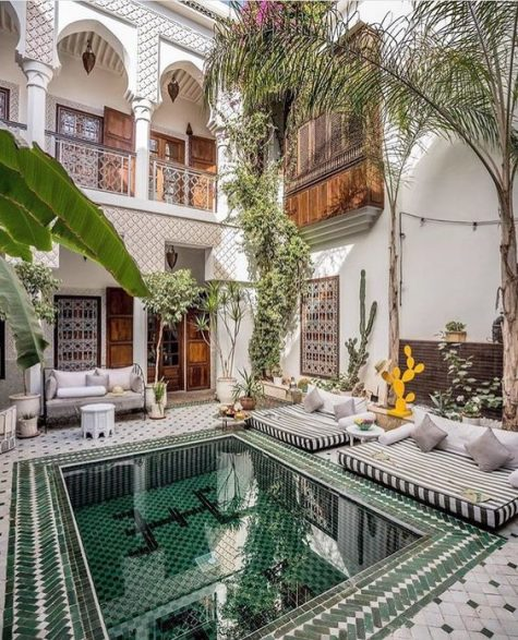 a gorgeous Moroccan pool patio with mattresses and pillows, a bench, side tables and potted plants