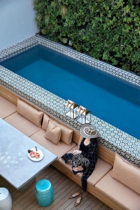a super long and narrow pool fully clad with Moroccan tiles and with a comfortable long sofa to line it up