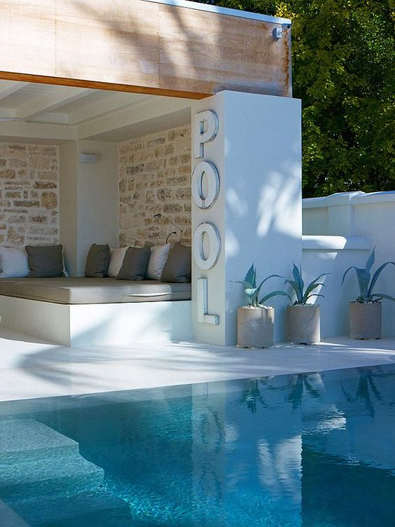 a cozy pool cabana with a built-in daybed, potted plants and a sign is a stylish minimal idea