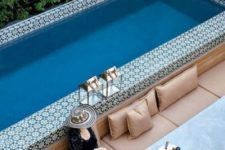 20 a long built-in bench with pillows, a dining table and side tables and ottomans by a pool clad with Moroccan tiles