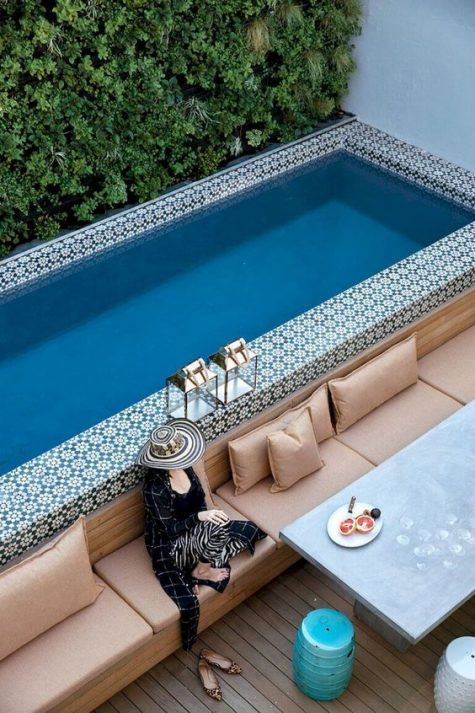 a long built-in bench with pillows, a dining table and side tables and ottomans by a pool clad with Moroccan tiles