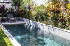 20 a lush tropical garden, a couple of loungers and a small and narrow pool clad with mosaic tiles