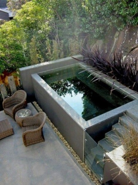 a small raised swimming pool with a ladder and a glass door plus a terrace with wicker furniture by its side