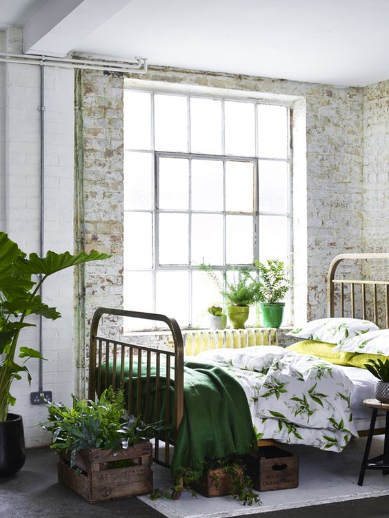 an industrial meets vintage bedroom with botanical print bedding and an emerald blanket
