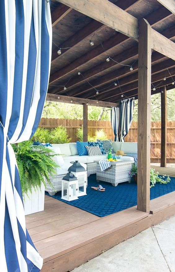 a gorgeous pool cabana done in blues and white with wicker furniture, lanterns and rugs plus potted ferns