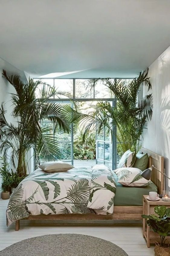 a light-filled bedroom with palm trees in pots and matching bedding plus a garden behind the wall