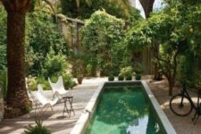 21 a lush tropical garden, a small wooden deck with butterfly chairs with a long and narrow pool in concrete