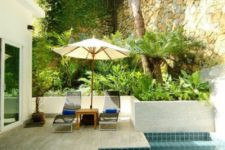 21 a stone clad pool deck with loungers and an umbrella plus a small backyard pool clad with turquoise tiles inside