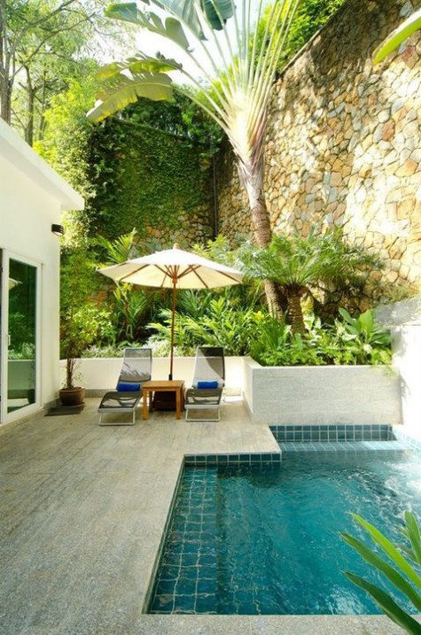 a stone clad pool deck with loungers and an umbrella plus a small backyard pool clad with turquoise tiles inside