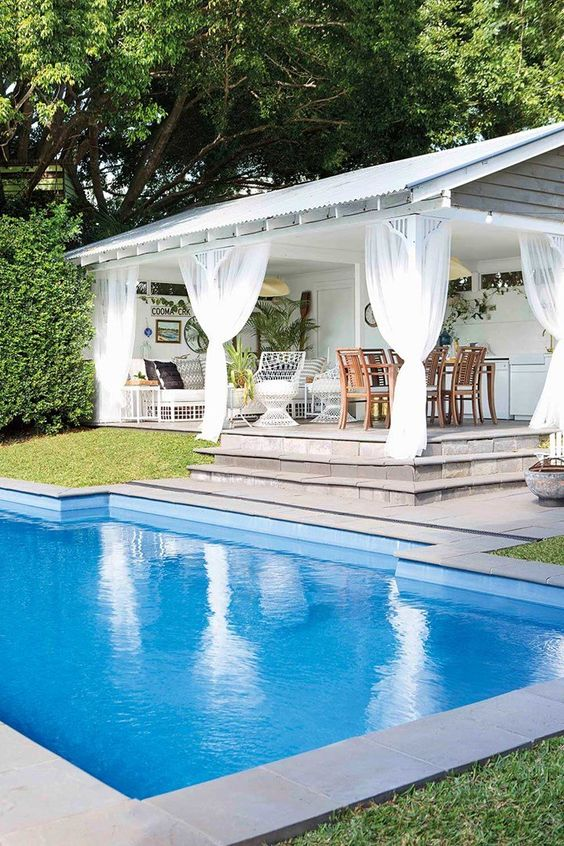a large pool cabana representing a living room, a kitchen and a dining room, with relaxed tropical boho decor