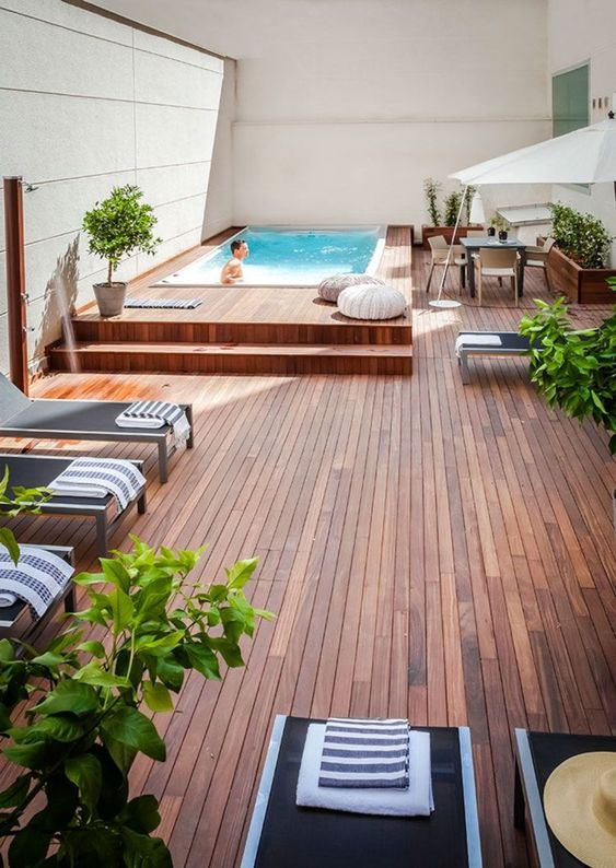 a simple contemporary pool deck with loungers, a dining space and soem crochet ottomans looks very lively