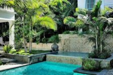 22 a stylish backyard deck clad with stone and with wooden loungers and with a small pool done with turquoise tiles inside