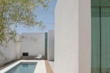 23 a clean minimalist backyard with a small narrow pool clad with white tiles