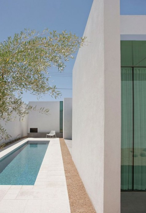 a clean minimalist backyard with a small narrow pool clad with white tiles