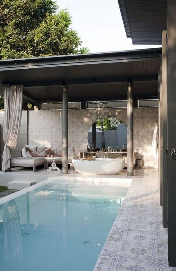 a luxurious pool cabana with an outdoor tub, some upholstered furniture, a round mirror and console plus a pool to create an ultimate oasis