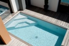 23 a stylish minimalist wooden deck with a blue pool and a single chair with a matching pillow is ultra-modern