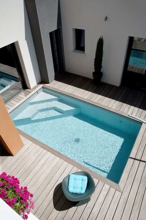 a stylish minimalist wooden deck with a blue pool and a single chair with a matching pillow is ultra-modern