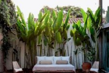 23 a tropical pool deck with a couple of loungers, an upholstered sofa, a jute ottoman and potted plants