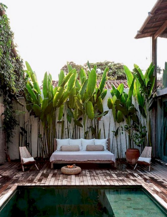 a tropical pool deck with a couple of loungers, an upholstered sofa, a jute ottoman and potted plants