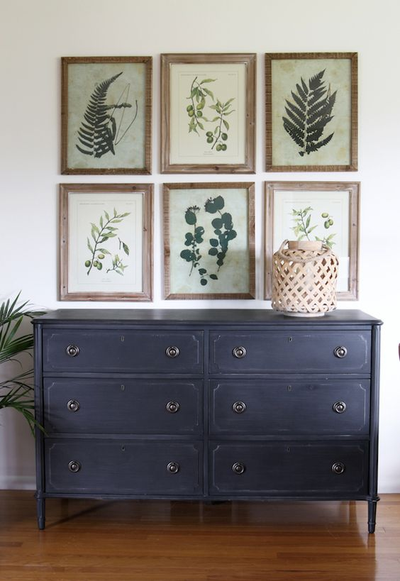 a vintage navy sideboard and a gallery wall of vintage botanicals in frames