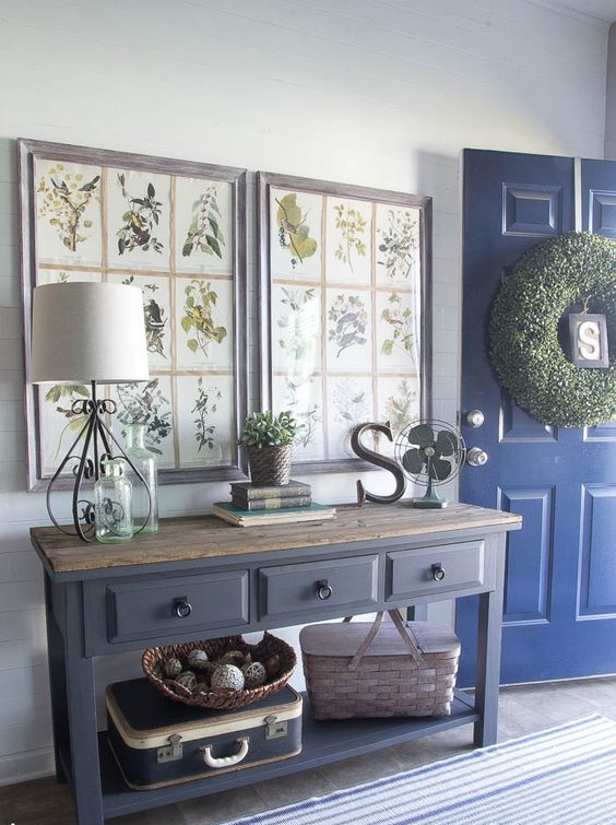 a farmhouse entryway with large artworks of botanical prints in frames to highlight the style of the space