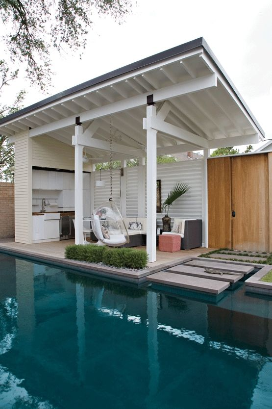 a stylish contemporary pool cabana with a living space and a kitchen, with a hanging acrylic chair and potted greenery
