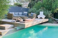24 a wooden deck over the pool with wicker furniture and wooden loungers, with pillows and cushions