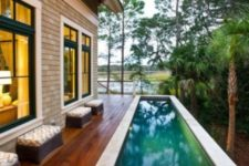 25 a small stained wooden deck with a long and narrow pool clad with stone is a chic idea for a tiny backyard
