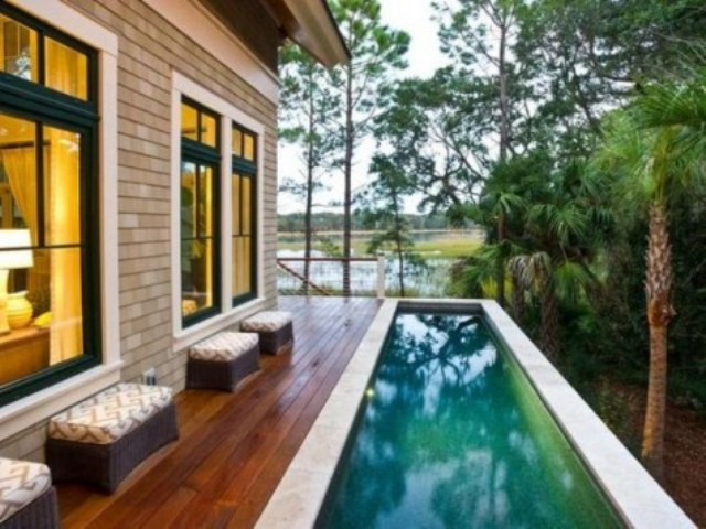 a small stained wooden deck with a long and narrow pool clad with stone is a chic idea for a tiny backyard