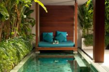 25 a welcoming tropical backyard with a rustic cabana, a small pool with mosaic tiles and built-in benches