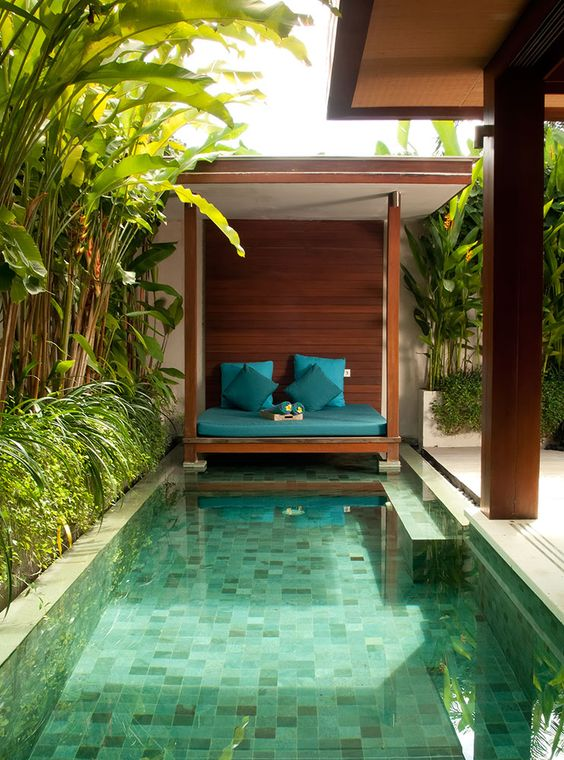 a welcoming tropical backyard with a rustic cabana, a small pool with mosaic tiles and built-in benches