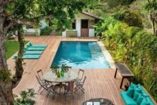 25 a wooden deck with a corner sofa, a living edge coffee table, a dining area and some cushions next to the pool