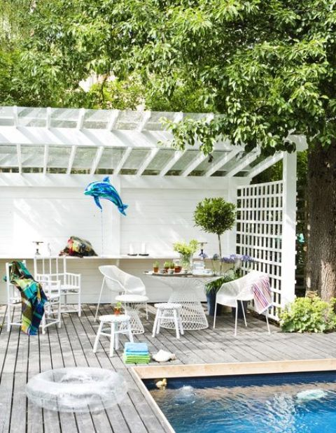 an entertaining pool cabana with a dining zone and a cocktail area, with potted plants, wooden and metal furniture and candles