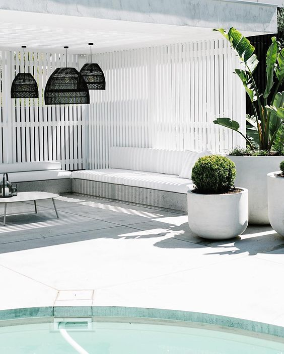 a minimalist white pool cabana with black pendant lamps, simple wooden benches with upholstery, potted plants and a coffee table