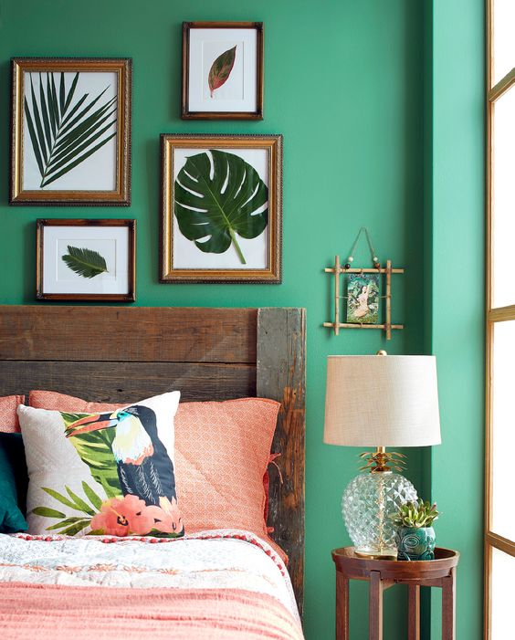 a tropical bedroom with a small gallery wall of real leaves that highlights the theme of decor
