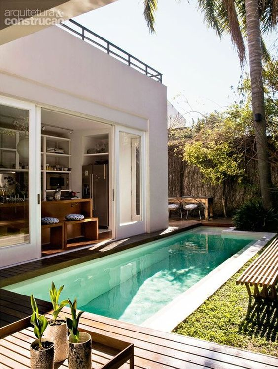 a welcoming deck with wooden plank benches, a small narrow pool and a dining zone behind the house