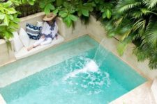 26 a wonderful tropical backyard all clad with sandy shaded tiles and with a small pool with a waterfall