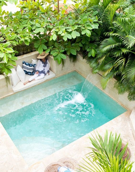 a wonderful tropical backyard all clad with sandy shaded tiles and with a small pool with a waterfall