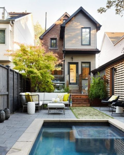an outdoor sofa, coffee table, some lanterns and side tables for a stylish and comfy pool deck setup