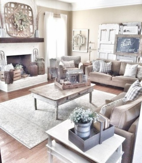 a cozy and neutral farmhouse living room with upholstered furniture, a shabby chic coffee table, a neutral fireplace and vintage doors for decor