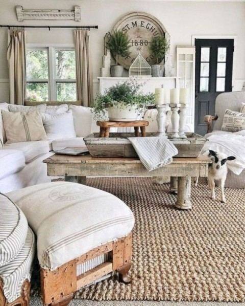 a cozy farmhouse living room with neutral upholstered furniture, a wooden coffee table and a stool on casters plus whitewashed candle holders