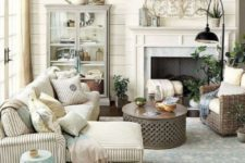 a cozy farmhouse space with a non-working fireplace, neutral upholstery, an aqua side table, a glass armoire