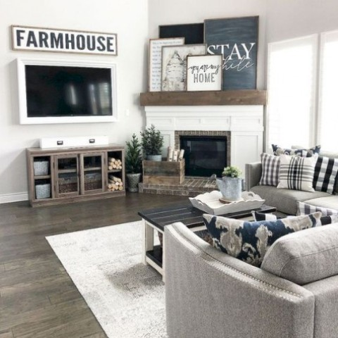 a farmhouse living room done in neutrals, with grey upholstered furniture, a rustic coffee table, a gallery wall on the mantel